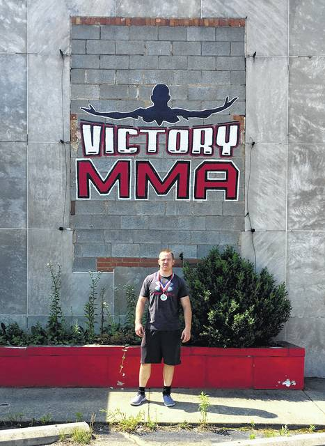 Adams County Sheriff's Deputy Brandan Holliday stands in front of Victory MMA in Canton on Wednesday. Holliday won the traditional wrestling gold medal at the annual Ohio Police and Fire Games.