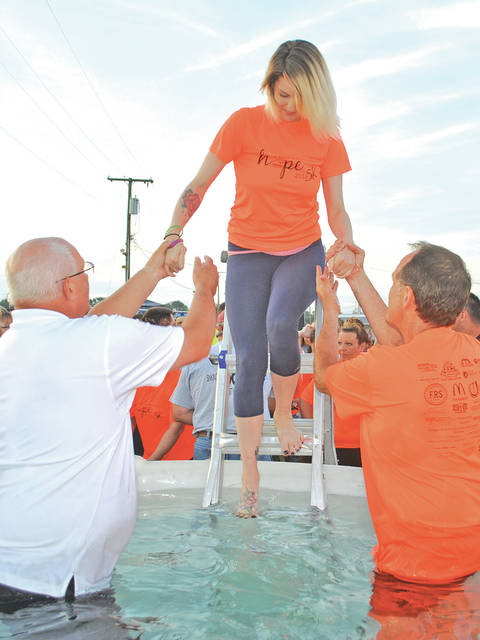 Chasity Wright of Columbus is helped into a baptismal tank by Steve Allen, left, and Jim Bush, right, during the Hope Over Heroin event held last Friday and Saturday at the Highland County Fairgrounds in Hillsboro. About 60 people were baptized over the two days.
