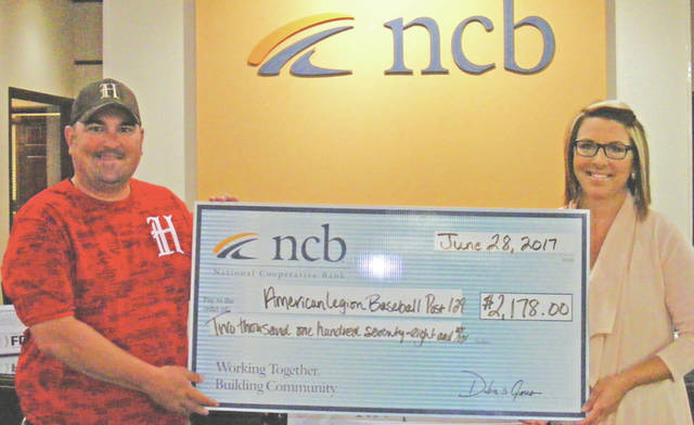 NCB recently donated $2,178 to the Hillsboro American Legion Baseball Post 129 teaqm. The money was used to purchase new uniforms for the team. Pictured are Scott Morgan, left, general manager and coach for the team, and Jocelyn Leeth, NCB assistant branch manager.