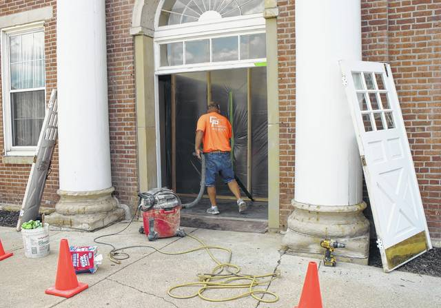 Randy Parson, an employee of Tira Builders of Hillsboro, cleans up the front entryway of the Highland County Courthouse Tuesday afternoon in preparation for the installation of new front doors. Work continues on restoring the interior and exterior of the courthouse and adjacent Highland County Prosecutor's Office, including the office's HVAC system, which has caused maintenance headaches - and even fires - for years.