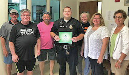 Members of Greening Greater Greenfield (G3) recently presented the Greenfield Police Department with its monthly Go-Getter for the Better award for the department's efforts in making Greenfield a better place to live, work, do business and play. Along with the award, G3 members supplied meals for each work shift for the day at the station. In this picture, the group presents patrolman Robbie Hamilton with his award.