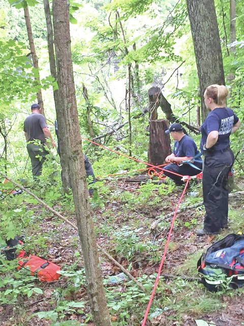 Local emergency responders set up lines to rescue a man and two dogs trapped Thursday in the Rocky Fork Gorge.