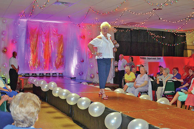 Some of the models that participated in the Ladies Day Out Fashion Show Catwalk For A Cause on Wednesday at the Highland County Senior Citizens Center are shown. In one photo, Joanetta Fetters models on the elevated walkway. In the other photo are some of the models including Jackie Noble, Rose Fleming, Vicki Fligor, Arlane Bick, Marilyn Bain, Anna Griffith, Luise Curtis, Joanetta Fetters, Sue Thornhill, Ruth Crabtree, Katelyn Tarr (young girl in front) and Pat Ziesemer. Not pictured are two young girls that was also served as models, Aubree Hoop and Addie Hoop.