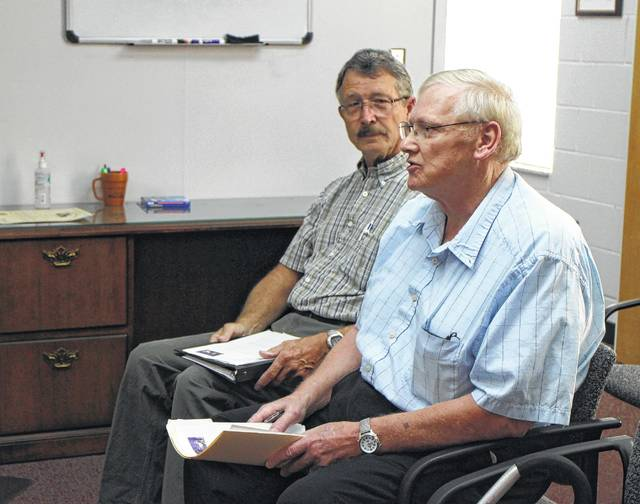 Bob Prosek, foreground, and Bob Jones of the Highland County Airport Authority speak to the Highland County Board of Commissioners Wednesday regarding the purchase of a hangar at the Highland County Airport.