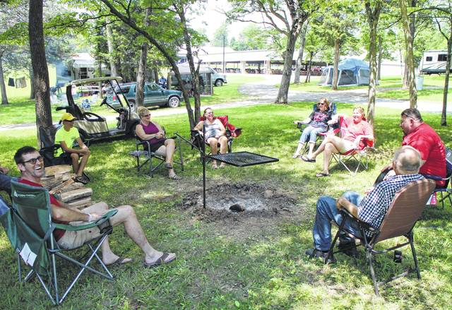 A group of family and friends gathers around a campfire Monday afternoon at Restoration Acres for Hillsboro Family Camp, a yearly event that draws thousands from around the country to worship, hear sermons and enjoy each other's company in the great outdoors.