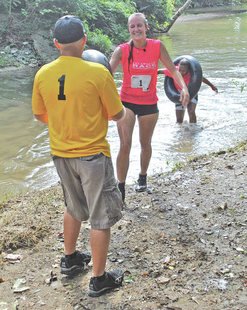A pair of competitors receive assistance from a helper as they exit a challenge during last year's Amazing Race of Highland County.