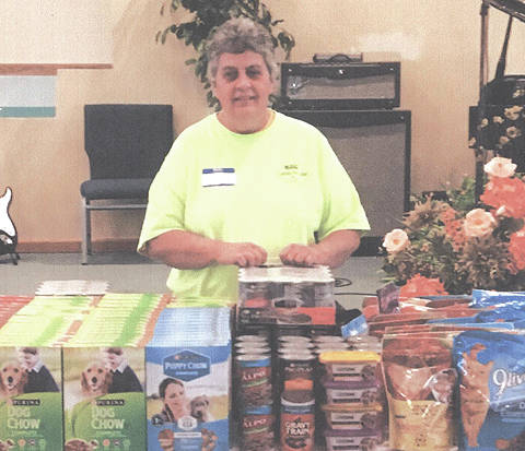 Sally Hinton is pictured at Greater Life Assembly Church with some of the food she gave away at her most recent pantry for dogs and cats.