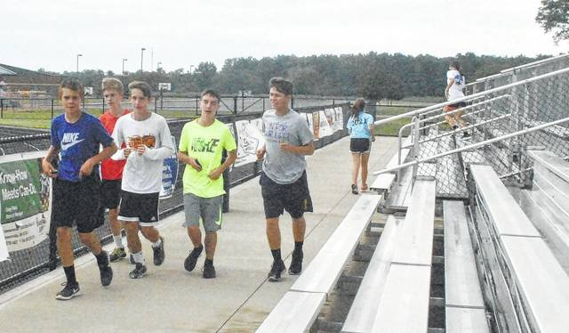 Members of the Lynchburg-Clay cross country team do a warmup run before the start of practice.