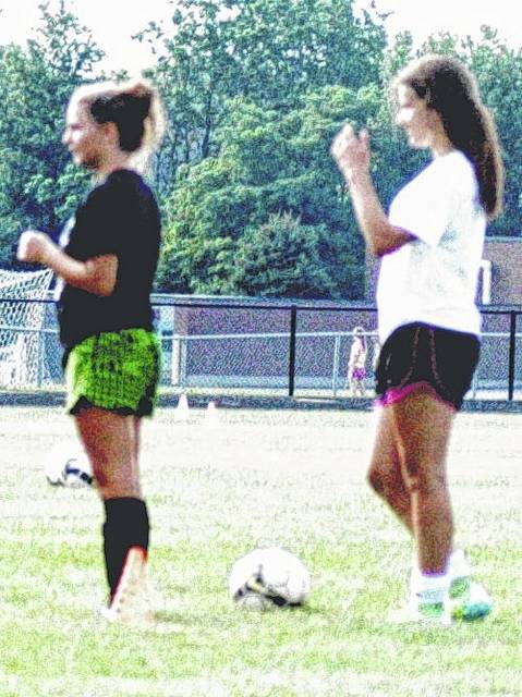 Members of the Lady Mustangs soccer team stand ready to enter a drill at practice.