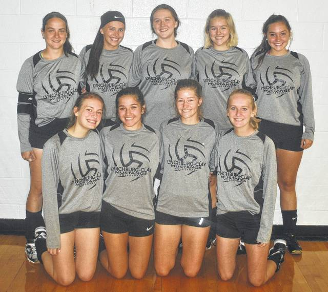 Members of the Lynchburg-Clay Lady Mustangs volleyball team pose for a picture before practice.