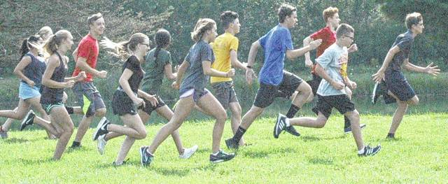 The McClain Tigers cross country team does a warm up run before practice begins.