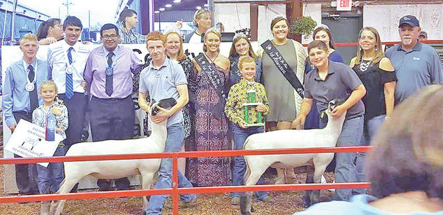Jeff Kline, with the sheep on the left, helps his cousin, Owen Kline, on right, with the winners of the Reserve Champion Pen of Two at the 2017 Ross County Fair.