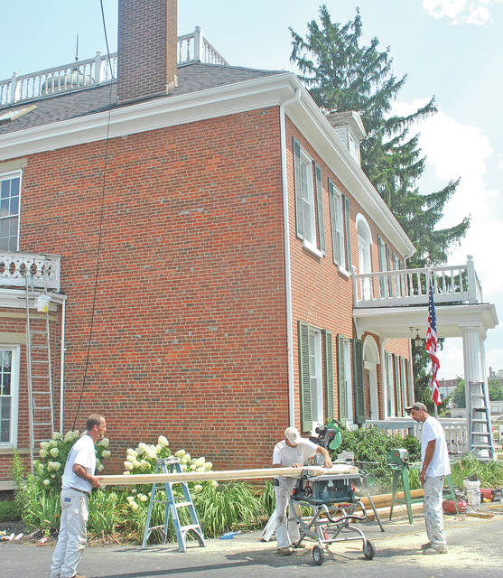 Workers with Precision Painting and Remodeling fabricate wood Wednesday for repairs to the historic Scott House on West Main Street in Hillsboro.