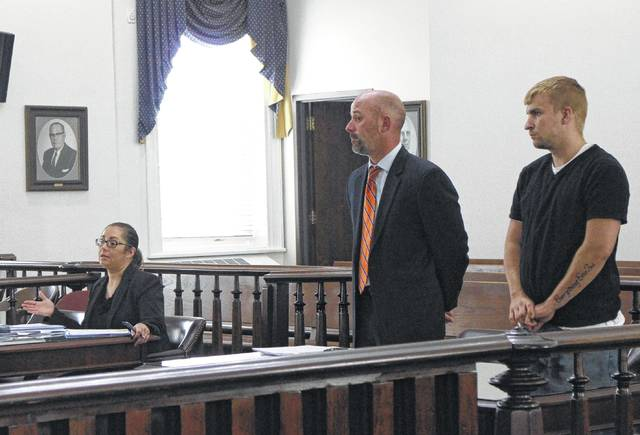 Shawn Reese, right, stands with defense attorney J.D. Wagoner, center, as Highland County Prosecuting Attorney Anneka Collins, seated, speaks to the judge Rocky Coss during a Tuesday hearing in Highland County Common Pleas Court.