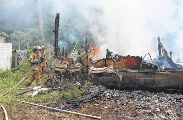 Firefighters work to extinguish a fire Thursday afternoon on Butters Road near Marshall. The blaze burned a large structure to the ground, destroyed a nearby camper and scorched the side of a pickup truck. Emergency crews had the fire under control in about an hour and a half. The cause of the fire was unknown Thursday afternoon, and no further information was immediately available.