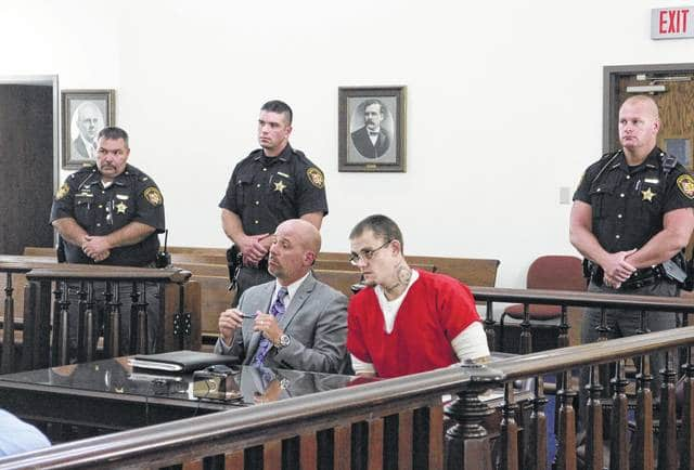 Jeffrey Ryan Holsinger, right, sits in court during an arraignment Tuesday with defense attorney J.D. Wagoner.