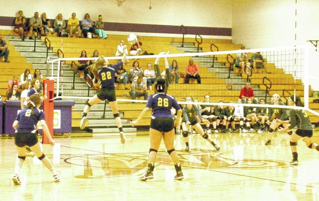 Hunter Scott of McClain attacks the net as Amber DeBoard of Lynchburg-Clay attempts to block on Wednesday in a cross-county volleyball match-up at McClain High School.