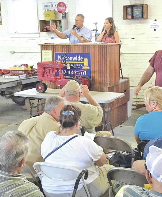 Ken and Kara Juillerat of Nationwide Auctions & Realty are shown auctioning off a McCormick Farmall M pedal tractor for $11,500 Saturday in Mowrystown.