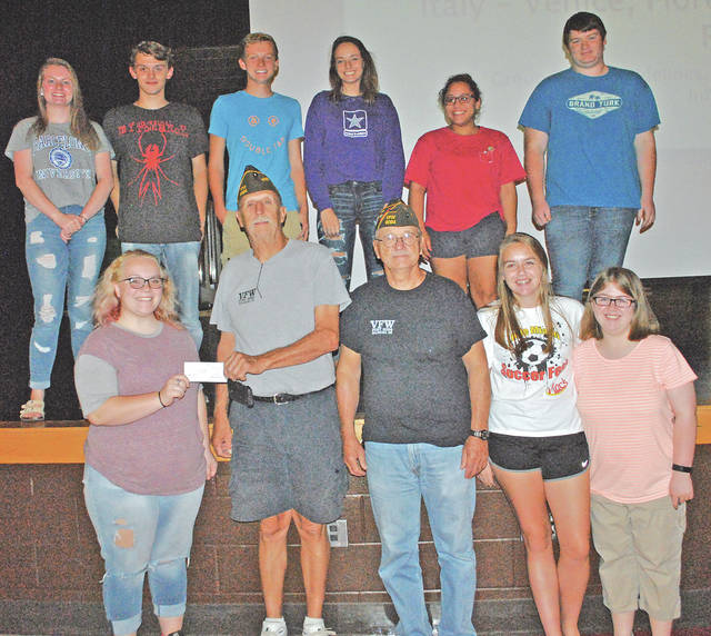 Rick Wilkin and Dwight Reynolds of Hillsboro VFW Post 9094 present a check for $1,000 to Olivia Wilson and some of the other Hillsboro High School students who will be taking an educational excursion to Venice, Florence and Rome, Italy in June of next year. Hillsboro student Ellie Elmore wrote a letter to the VFW asking for financial help with the trip and the VFW responded. Forty people will be making the trip to Italy including 25 Hillsboro students, five chaperones and 10 other adults that will be traveling with the group. The students will be holding fundraisers, including an upcoming popcorn sale, to raise more money for the trip.
