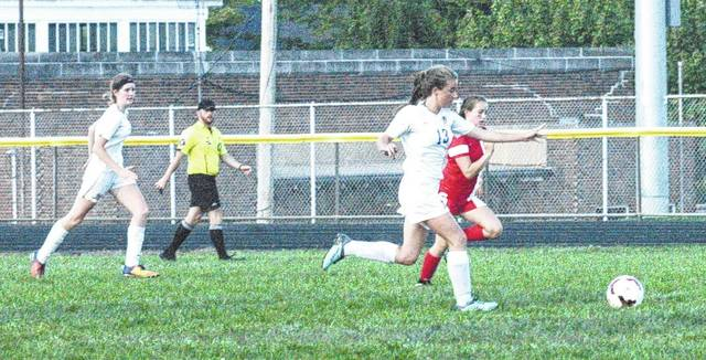 Peyton Voss (13) tries to advance the ball against Jackson during and FAC soccer match at McClain High School on Thursday.