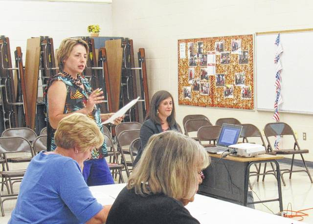 Rainsboro Elementary Principal Quincey Gray (standing) speaks to Greenfield Exempted Village Board of Education members Monday. Curriculum director Alisa Barrett is seated in the background.