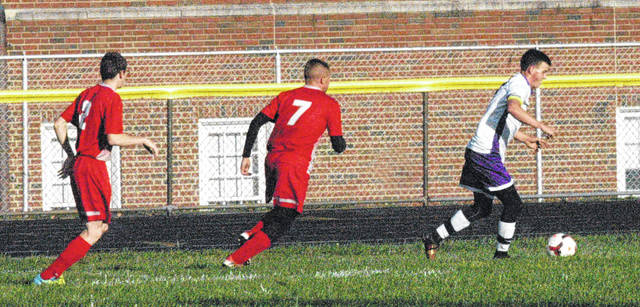 McClain senior Johnny Free advances the ball past two Westfall defenders on Monday at Greenfield High School.