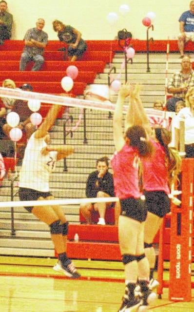 """Two Lady Indians block a spike attempt by the Lady Cavaliers on Tuesday at Hillsboro High School in the Lady Indians """"Volley for the Cure"""" game."""