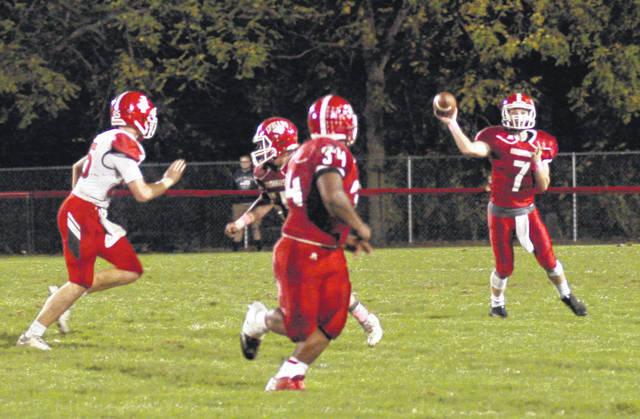 Mason Swayne (7) begins to throw as pass to Deon Burns (34) late in the first half against the Jackson Ironmen on Friday at Richards Memorial Field in Hillsboro.