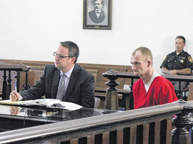 Jesse Roads, right, sits in court Tuesday with defense attorney Denny Kirk. Roads pled guilty to two counts of forgery and was sentenced to a year and a half in prison.