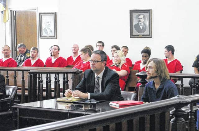 Travis Tracy, right, sits in court Thursday with defense attorney Denny Kirk, left, and a host of prisoners from the Highland County jail.