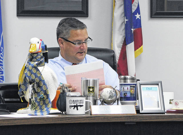 Highland County Board of Commissioners President Shane Wilkin reviews notes during a Wednesday commissioners meeting. Also shown is the Hillsboro Rotary Club duck, which ended up in Wilkin's possession this week as part of a light-hearted Rotary ritual.