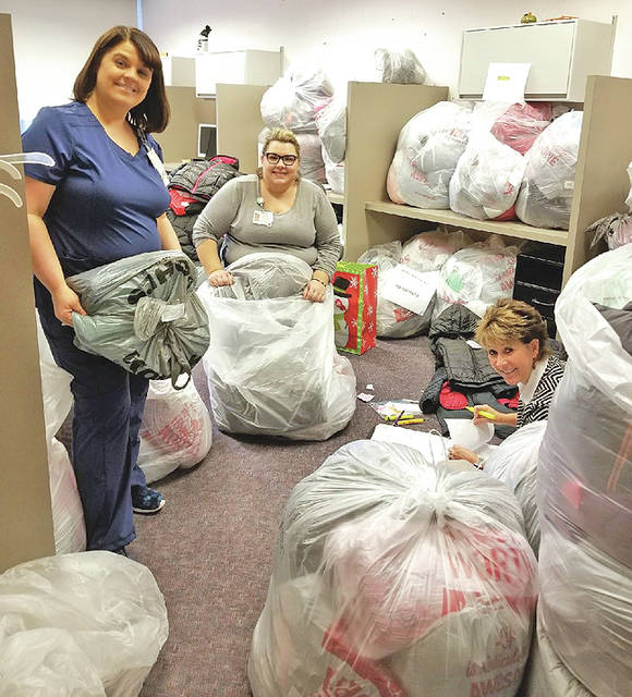 Adena employees Jackie Rebman, Shannon Morgan and Robin Berno sort through and prepare to deliver some of the more than 1,100 new coats purchased by Adena caregivers for area school children.