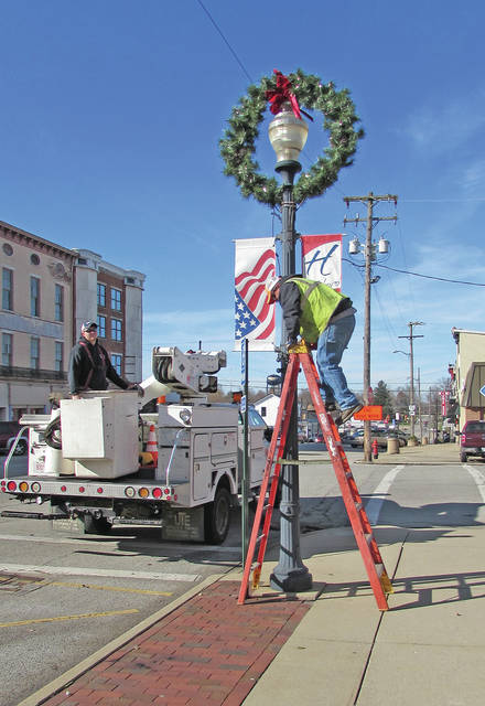 City of Hillsboro employees are pictured late Monday morning installing Christmas decorations on light poles in the uptown area.