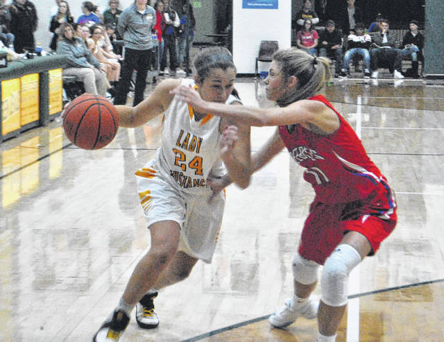 Peyton Scott drives to the basket against a Peebles Lady Indians defender on Friday night at North Adams High School during the SHAC preview.