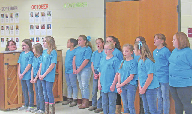 """Elementary music teacher Vicki Mikkelson (at the piano) leads fifth-grade honor choir members in a performance of """"All Things Bright and Beautiful"""" at Monday's Greenfield Exempted Schools Board of Education meeting."""
