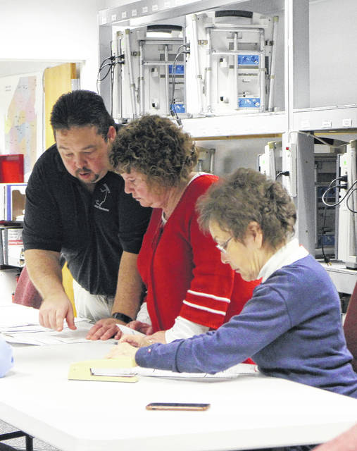 From left, elections administrator Steve Witham and office director Debbie Craycraft of the Highland County Board of Elections review paperwork Tuesday evening with Highland County Democratic Party Chair Dinah Phillips at the board of elections office.