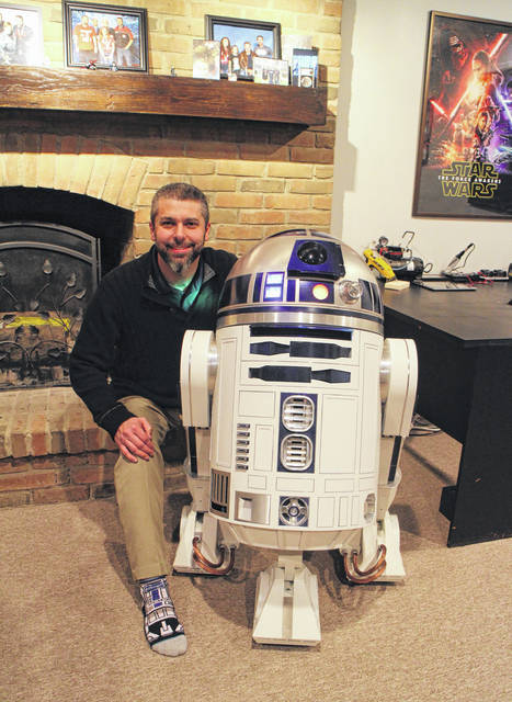 Josh Montgomery kneels next to his exact replica of R2-D2, the beloved droid featured in the Star Wars franchise.
