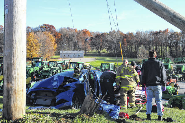 Emergency crews had to climb through a tangle of wires Friday to extricate a man from a wrecked vehicle on U.S. Route 50 in front of Five Points Implement Co., Inc.