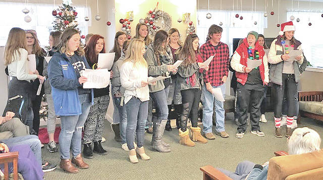 """The Hillsboro FFA chapter visited the Heartland of Hillsboro and Bell Gardens facilities this month to sing Christmas carols including """"Jingle Bells,"""" """"Santa Claus is Coming to Town,"""" and """"Rudolph the Red 'Nosed Reindeer"""" to bring Christmas cheer to the residents. Katie Craig said, """"This was a great way to spread happiness throughout the community."""" At the conclusion of caroling the FFA members went to Walmart to purchase gifts for Highland County families in need for the Christmas season. The chapter bought winter clothing and toys for them. The next day the FFA classes wrapped the gifts that were purchased to take to the families. The chapter also donated boxes of apples from the fruit sale. Pictured are FFA members singing Christmas carols at Bell Gardens."""
