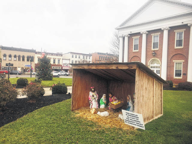 A nativity scene placed annually by the Yuellig family is shown in the foreground, with other Christmas decorations across the grounds of the Highland County Courthouse in Hillsboro.