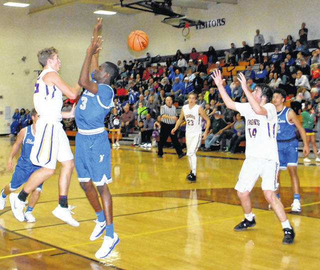 Garrison Banks passes over the head of Blue Lions defender Blaise Tayose to a cutting Devin Carter at McClain High School on Tuesday.