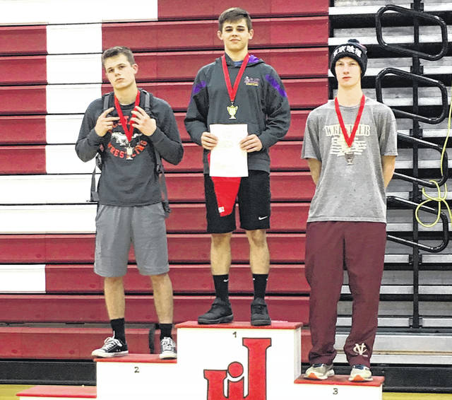 Keegan Rawlins poses with the second and third place finishers on the podium at Jackson High School after winning the 152 pound weight class.