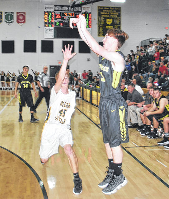 Noble Walker of Lynchburg-Clay shoots a three in the third quarter at North Adams High School as Colt Shumaker contests.