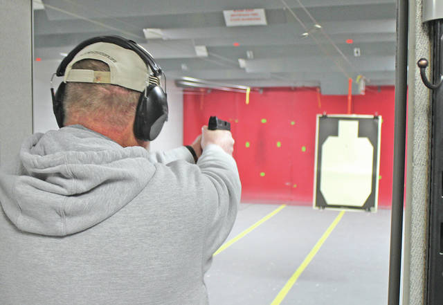 Chuck Morris opens fire at a paper target Friday evening. Morris is a National Rifle Association-certified firearm instructor and the owner of Hightechredneck's, an indoor shooting range and computer repair service in New Vienna.