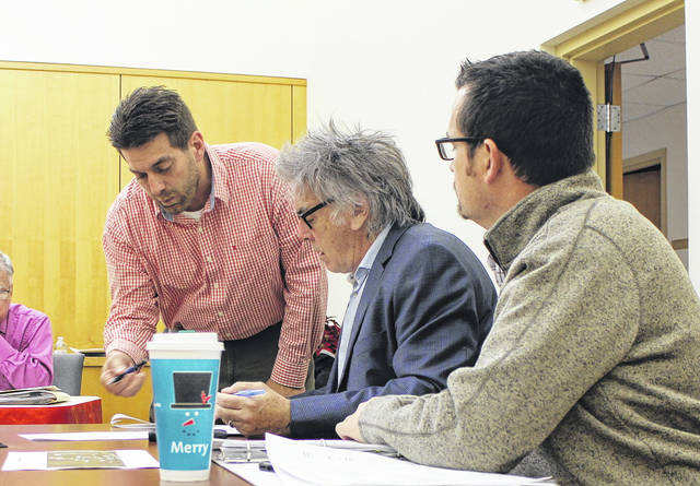 Hillsboro City Councilman Justin Harsha, left, reviews paperwork with Mayor Drew Hastings, center, and Safety and Service Director Mel McKenzie at Monday's city council meeting.