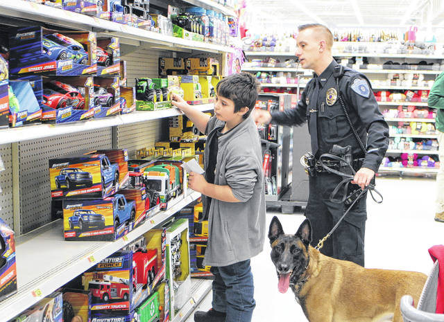 Aiyden Norris-Feltner, left, selects a toy tractor at the Hillsboro Walmart with Officer Adam Day of the Hillsboro Police Department. Also shown is the department's police canine, Harley.