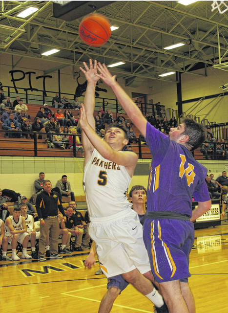 Devin Carter contests the shot of a Miami Trace player on Friday at Miami Trace High School in FAC basketball action.