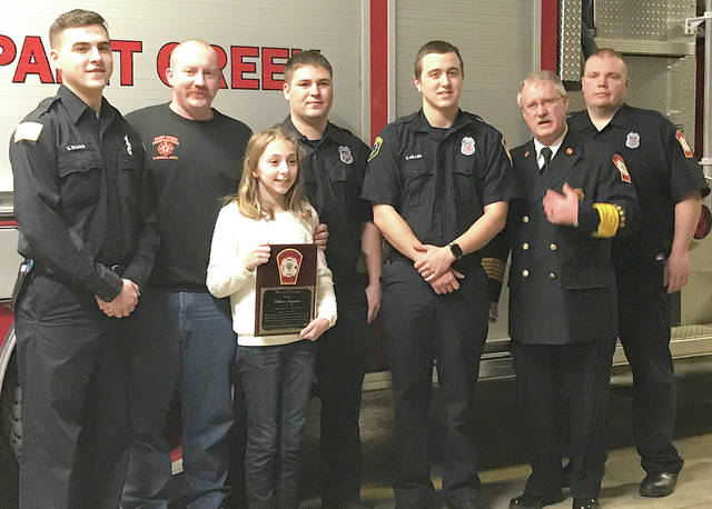 Twelve-year-old Lillian Fryman is pictured with her plaque and Paint Creek Joint EMS/Fire District personnel, from left, Nick Shanks, Lt. Adam Moran, Jeremiah Tennant, Rob Miller, chief Dave Manning and Rob McMahon.