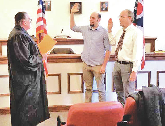 Highland County Court Judge Bob Judkins swears in new Greenfield Village Council members Eric Borsini, left, and Phil Clyburn, right, Monday morning.