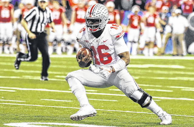 Ohio State quarterback J.T. Barrett runs with the ball during the Big Ten championship game in Lucas Oil Stadium in Indianapolis.